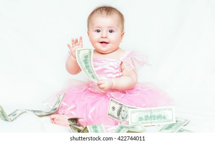 Cute infant baby girl in pink dress playing with money