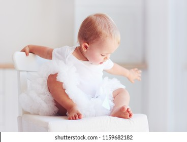 cute infant baby girl in tutu skirt sitting on chair