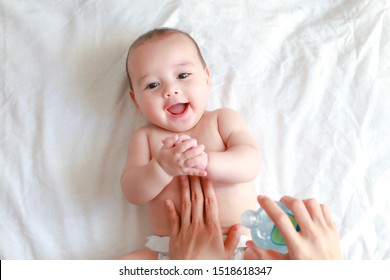 Cute infant boy massaging at home. Mother applying oil on her baby makes belly massage. Mixed race Asian-German kid