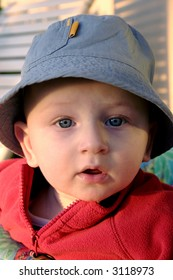 Cute infant boy in sun hat looking surprised