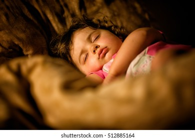 Cute infant girl sleeping in a bed with pillows and blankets