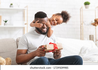 Cute ittle afro girl covering her dad eyes on Father's Day, daddy holding gift box, home interior, free space