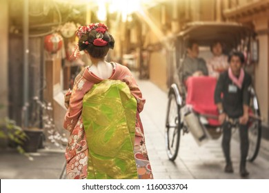 Cute Japanese geisha girl in traditional kimono costume walking in an alley of Kyoto in the sunset light crossing a rickshaw.