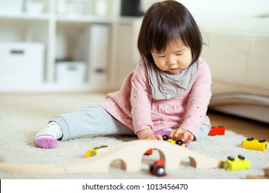 Cute japanese girl playing with toy blocks on the floor at home