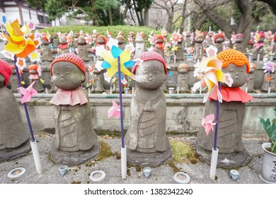 Cute jizo statues with small wind mills at a temple, Tokyo, Japan.