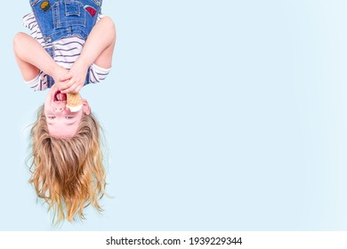 Cute joyful happy toddler child girl upside down with fluttering hair, eating vanilla ice cream. Summer vacation fun concept on blue background copy space