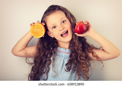 Cute joying grimacing happy kid girl with curly hair style holding citrus orange fruit and red apple in the hands. Toned closeup portrait