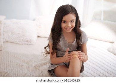 Cute kid applying band aid on wound at home