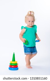 Cute kid blonde girl playing with color pyramid toy isolated on white background. Happy childhood and pre-school development of children.