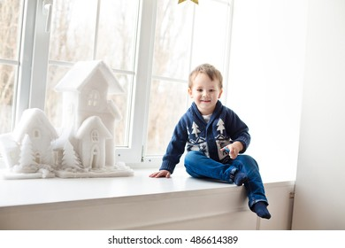 Cute kid in blue sweater sits on a window sill