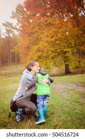 Cute kid boy hugging his mother on autumn meadow