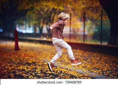 cute kid, boy in leather jacket having fun at autumn street, jumping and running around on carpet of fallen leaves