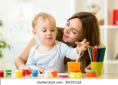 cute kid boy painting with paintbrush at home or day care center
