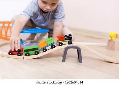Cute kid boy playing with toy railway road at home at floor, independent children's games