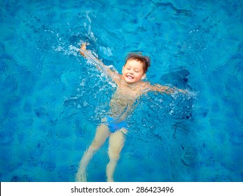 cute kid, boy swimming in pool water, top view
