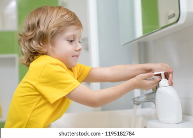 Cute kid boy washing his hands in bathroom