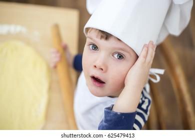 Cute kid in chef uniform baking