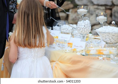 Cute kid choosing candies from table during wedding buffet