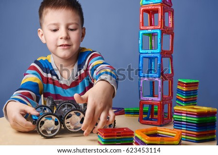 Cute kid crafting with magnetic construction set.