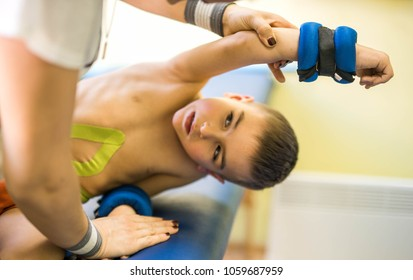 cute kid with disability has musculoskeletal therapy by doing exercises in body fixing belts