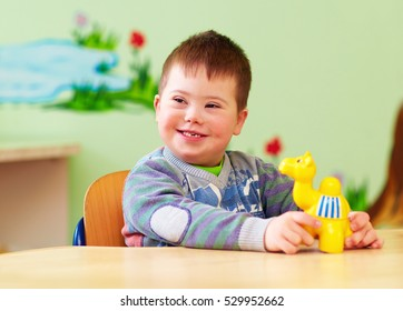 cute kid with down's syndrome playing in kindergarten