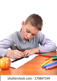 Cute Kid Drawing at the School Desk Isolated on the White Background