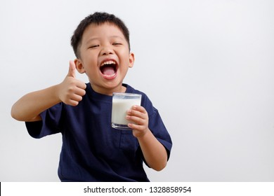 Cute kid drinking milk and showing thumb up sign, isolated on white background