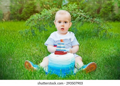 Cute kid eating his birthday cake on grass