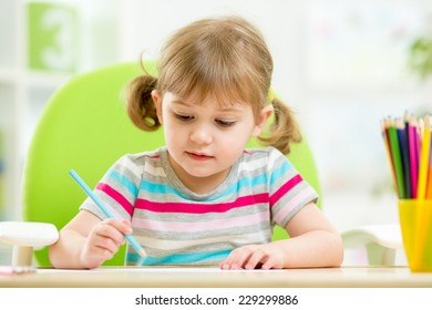 cute kid girl drawing with colourful pencils