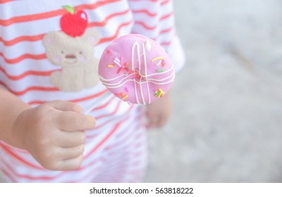 Cute kid girl eating sweet donuts. Girl holding unhealthy doughnut snack. sweets. doughnut. baby girl. child, kid