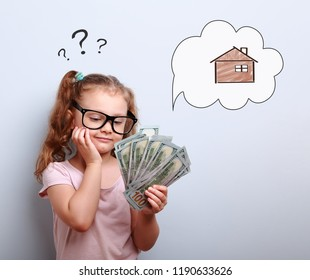 Cute kid girl in eyeglasses looking on money and thinking how spend its. Illustration bubble with house and question sign above on blue background
