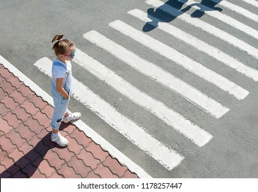 Cute kid girl in glasses and fashion clothes standing near the pedestrian crossing on the city street. Shadow and silhouette of mother and child crossing the street at zebra crosswalk. View from above