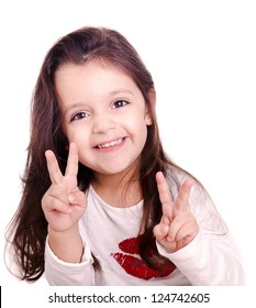 A cute kid girl making victory sign with her hands. This sign is also known as peace and love. The infant girl is isolated on white.