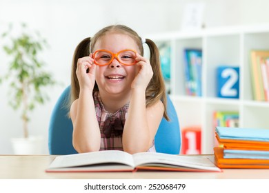 Cute kid girl reading a book while wearing glasses