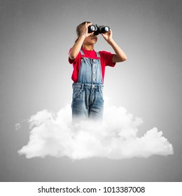 Cute kid girl sitting on cloud and looking in binoculars