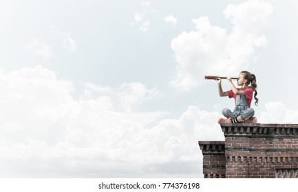 Cute kid girl sitting on house roof and looking in spyglass
