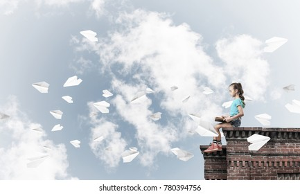 Cute kid girl sitting on building roof and reading book
