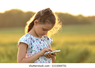 Cute kid girl texting sms on mobile phone with serious face on summer background. Closeup bright portrait