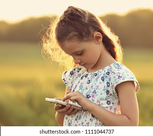 Cute kid girl texting sms on mobile phone with serious face on summer background. Closeup toned portrait
