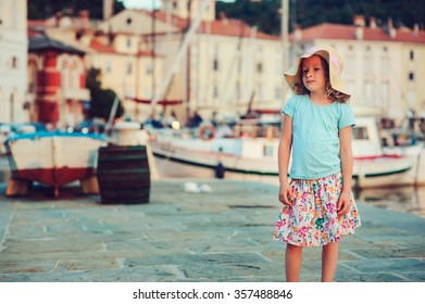 cute kid girl walking on coastline in Piran, Slovenia on summer vacation with city view on background