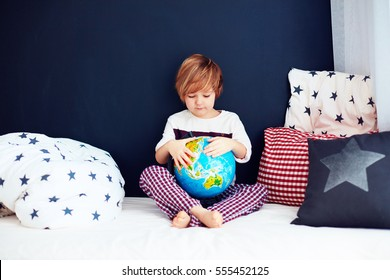 cute kid with the globe sitting in bed and exploring the new horizons