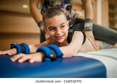 cute kid is going to have physical musculoskeletal therapy in rehabilitation center. Boy look at camera