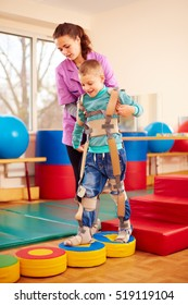 cute kid having physical musculoskeletal therapy in rehabilitation center