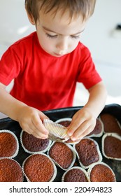 Cute kid helping in making cupcake with shallow depth of field