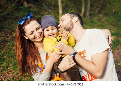 Cute kid and his parents walking in the forest