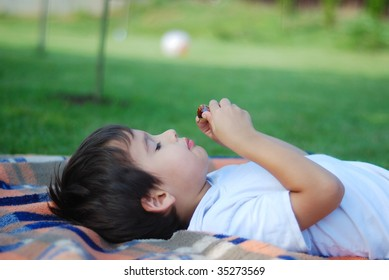 Cute kid is laying and eating fruit in beautiful environment
