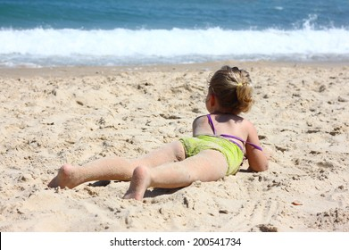 cute kid laying on sand beach looking at the sea. photographed under natural light during beach time activity