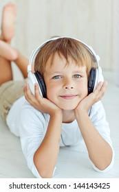 Cute kid listening to music on headphones and enjoying