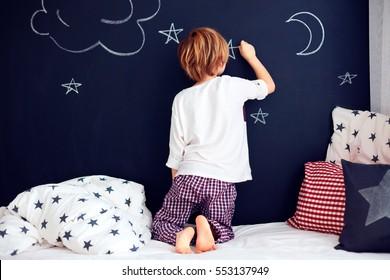 cute kid in pajamas painting chalkboard wall in his bedroom.