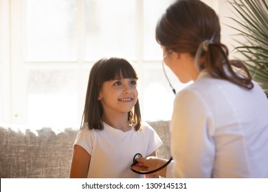 Cute kid patient visiting female doctor pediatrician nurse holding stethoscope examining happy little child girl doing pediatric checkup in hospital clinic, children medical health care concept
